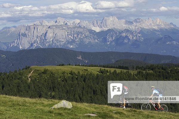 Mountainbiker und -bikerin auf der Hohen Reisch mit Blick auf die Dolomiten  Südtirol  Italien  Europa