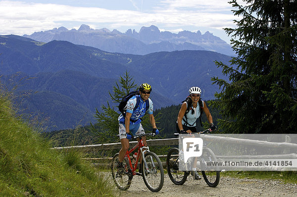 Mountainbiker und -bikerin bei der Auffahrt zur Öttenbacher Alm mit Blick auf die Dolomiten  Italien  Europa