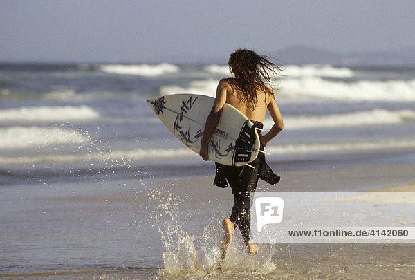 Junger Surfer rennt mit Surfbrett unter dem Arm über den Strand von Surfers Paradise  Gold Coast  Queensland  Australien