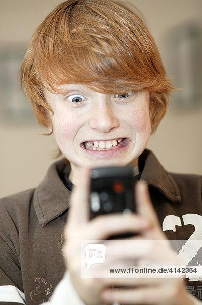 Junge spielt mit Handy