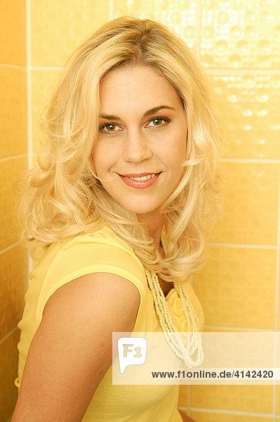 Junge blonde Frau im gelben Kleid posiert vor gelbem Hintergrund