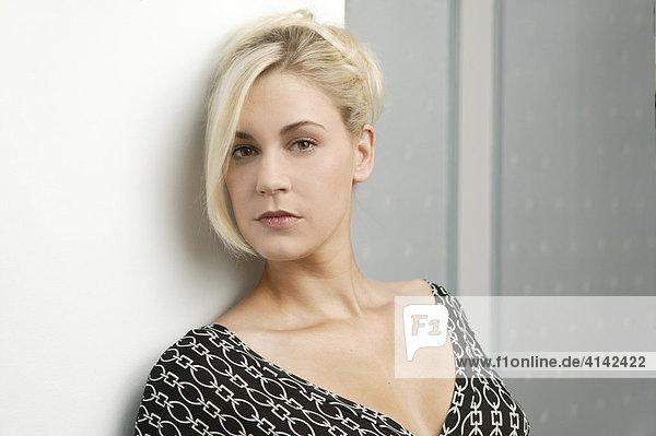 Junge blonde Frau im Abendkleid lehnt an der Wand