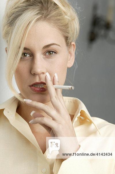 Junge blonde Frau mit Zigarette