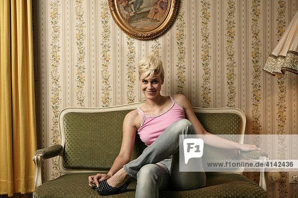 Junge  blonde Frau in Freizeitkleidung  sitzt auf Jugendstil-Sofa