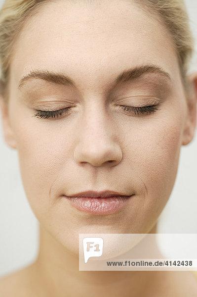 Junge  blonde Frau mit geschlossenen Augen  Gesicht in Nahaufnahme
