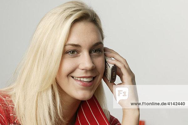 Junge  blonde Frau mit Handy