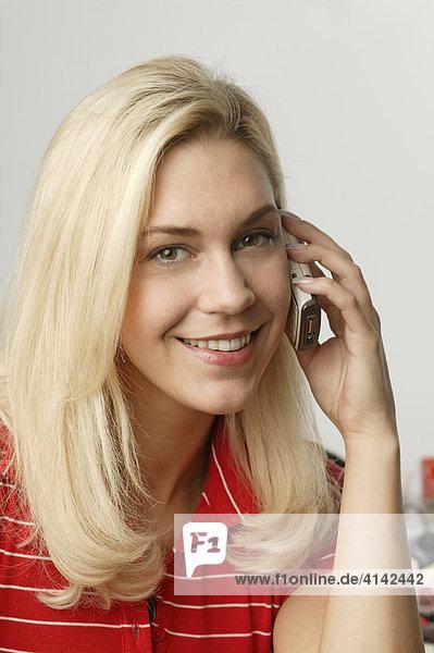 Junge  blonde Frau mit Handy  schaut in Kamera
