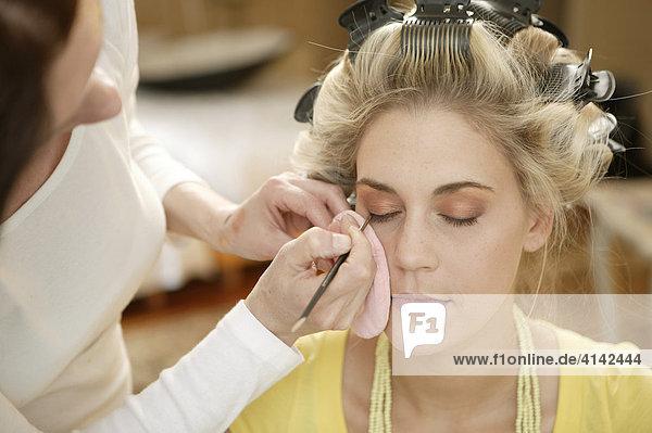 Blondes Fotomodell wird geschminkt
