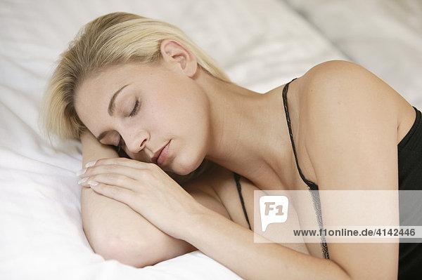 Junge  blonde Frau mit Negligé  liegt schlafend im Bett