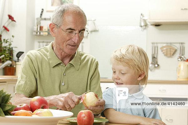 Opa schält Apfel für Enkel