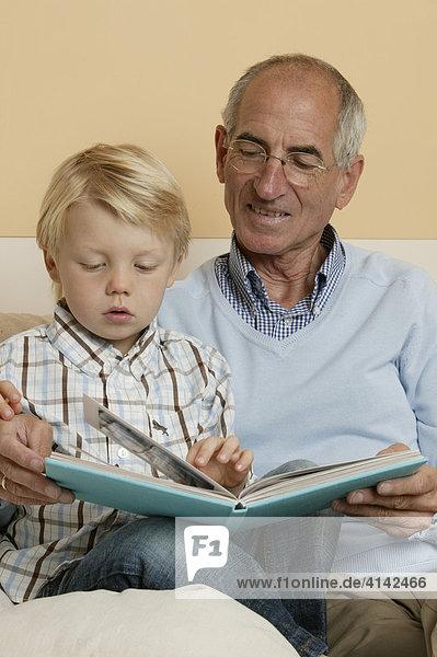 Opa sieht mit Enkel Fotoalbum an