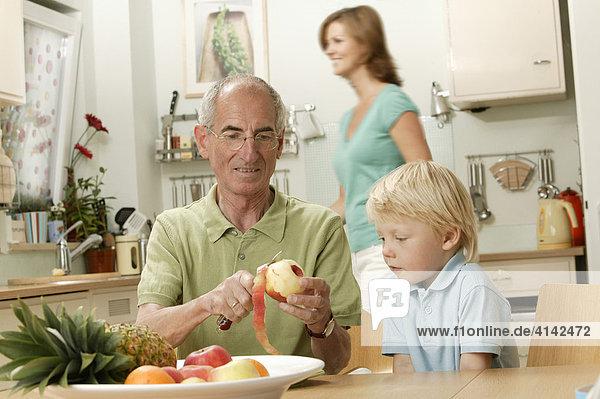 Opa schält Apfel für Enkel  junge Frau im Hintergrund