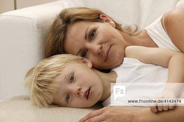 Mutter und Sohn kuscheln auf der Couch  Blick in Kamera