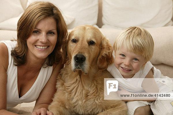 Frau mit Hund und Sohn vor dem Sofa  lächeln