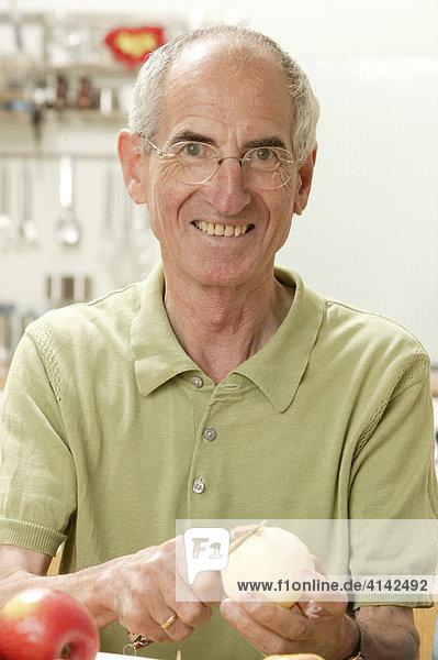 Älterer Mann schält Apfel in der Küche