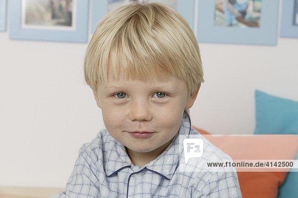 3-jähriger Junge im Schlafanzug  sitzt im Bett