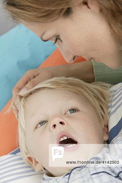 Mutter bringt ihren Sohn ins Bett  Kind gähnt