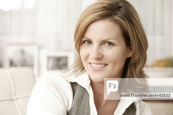 Junge Frau im Wohnzimmer  lächelt