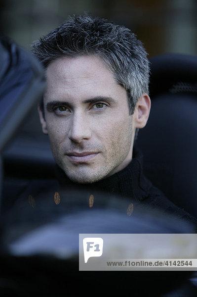 Portrait Mann im schwarzen Cabrio