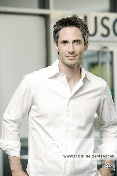Junger Mann im weißen Hemd  in Eingangshalle