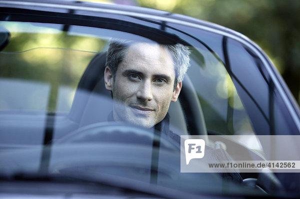 Mann im Sportwagen - Cabrio sieht durch die Windschutzscheibe