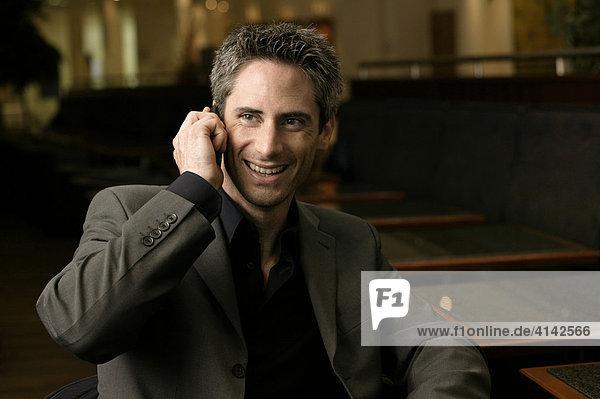 Mann im Anzug in Bar telefoniert mit Handy