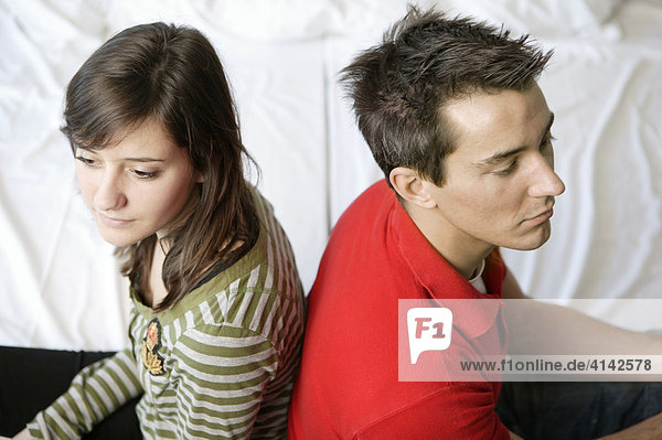 Junger Mann und junge Frau schweigen sich an  Rücken an Rücken