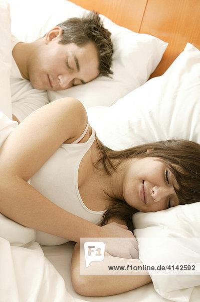 Junges Paar schläft im Bett  lächelnd