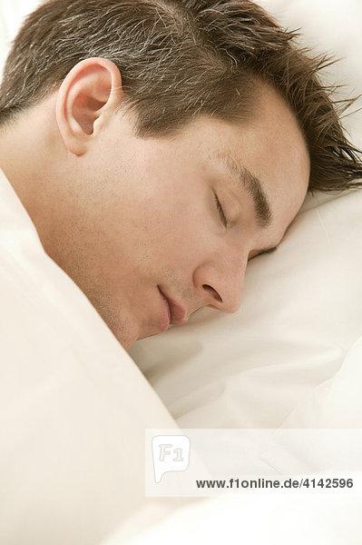 Junger Mann liegt im Bett und schläft