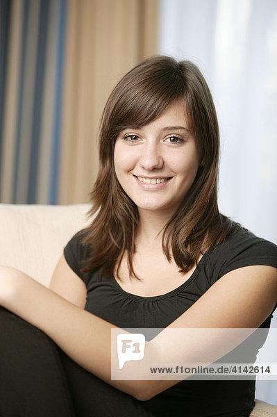 17-jähriges Mädchen sitzt auf Sofa und lächelt