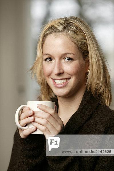 Junge Frau im dunklen Pullover lächelt  mit Tasse