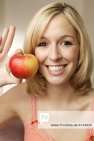 Junge  blonde Frau mit Apfel  lächelt