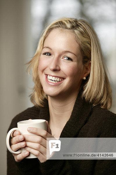 Junge  blonde Frau im dunklen Pullover mit Tasse  lacht