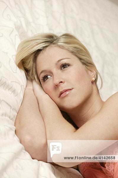 Junge  blonde Frau liegt im Bett  nachdenklich