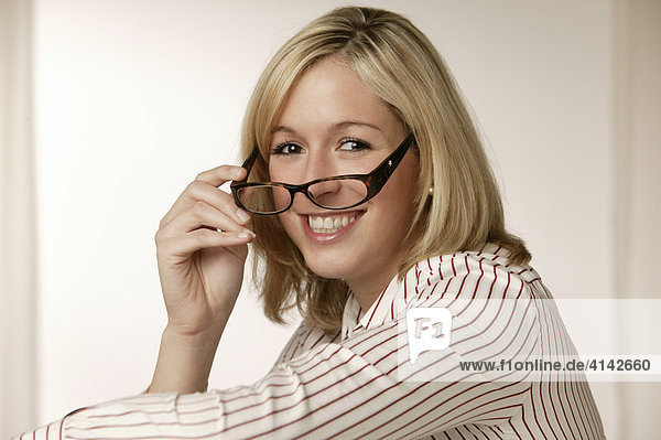 Junge  blonde Frau in gestreifter Bluse  lächelt  setzt Brille auf