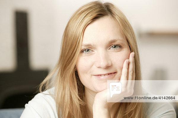 Blonde Frau lächelt  stützt sich mit einer Hand auf