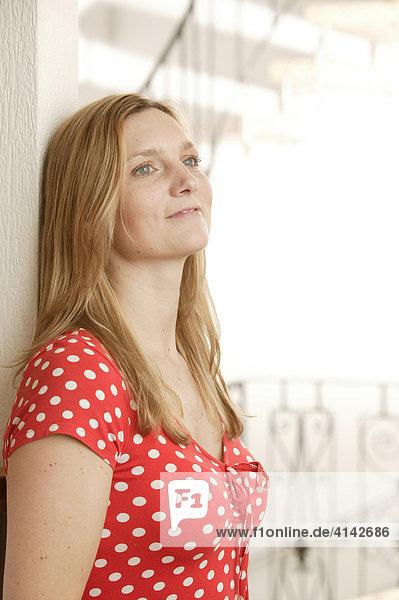 Blonde Frau lehnt an Wand  lächelt