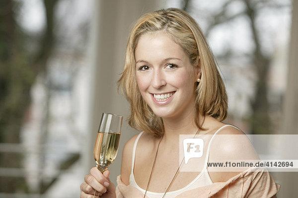 Junge  blonde Frau mit Sektglas  lächelt