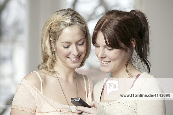 Two young women with a mobile phone