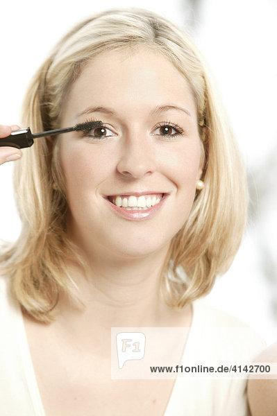 Junge  blonde Frau schminkt sich mit Wimpertusche