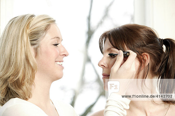 Blonde  junge Frau Frau schminkt ihre Freundin