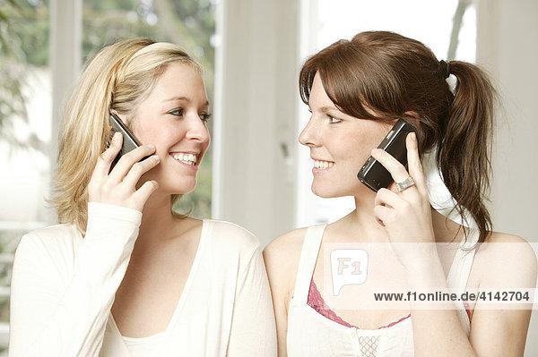 Zwei junge Frauen telefonieren mit ihren Handys  sehen sich an