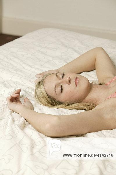 Junge  blonde Frau liegt ausgestreckt im Bett  schläft