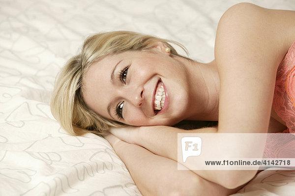 Junge  blonde Frau liegt im Bett  lacht