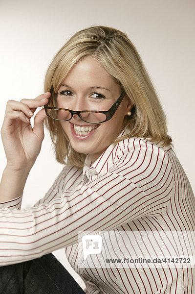 Junge  blonde Frau in gestreifter Bluse  lächelt  mit Brille