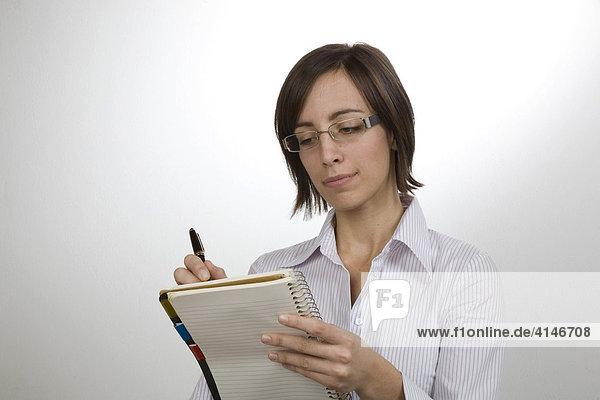 Sekretärin mit Block und Stift beim Diktat