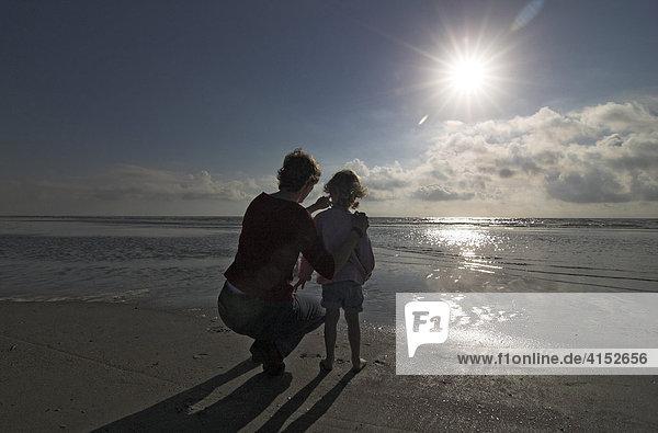 Junge Frau und ihre kleine Tochter hocken am Strand und schauen auf das Meer  Dänemark