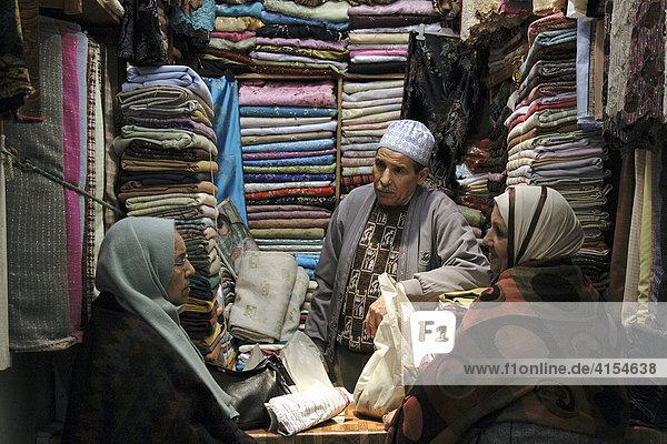Stoffhändler mit Kunden in einem Souk  Fes  Marokko