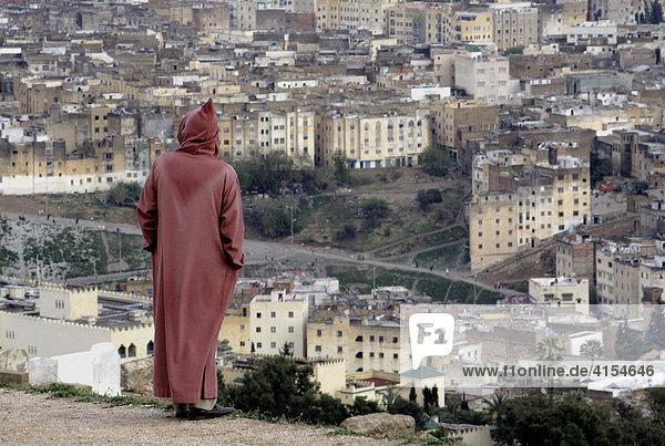 Mann in Djellabiah auf Aussichtshügel  Fes Marokko