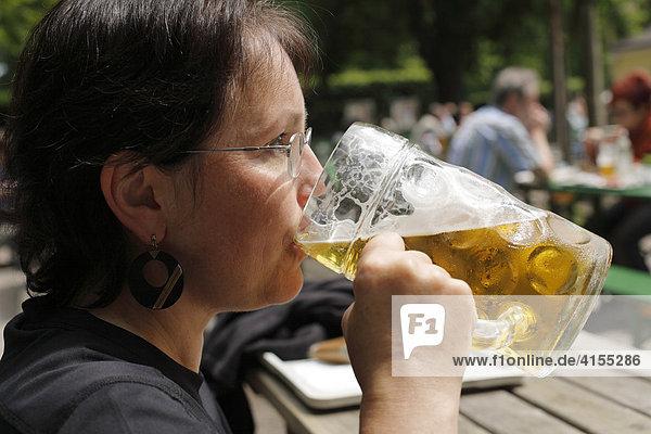 Woman drinking a litre of Spaten brand beer  Taxisgarten Beer Garden  Munich  Bavaria  Germany  Europe